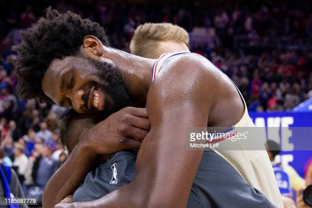 Joel Embiid of the Philadelphia 76ers embraces his former teammate TJ McConnell of the Indiana Pacers at the Wells Fargo Center on November 30 2019...