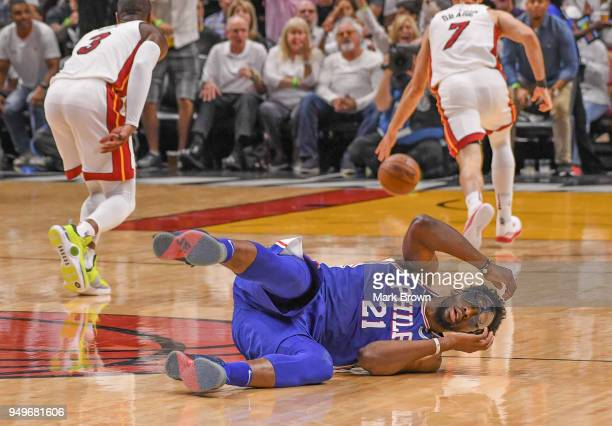 Joel Embiid of the Philadelphia 76ers falls on the court in the second quarter during the game against the Miami Heat in Game Four of Round One of...