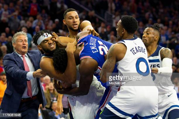 Joel Embiid of the Philadelphia 76ers gets in a fight with Karl-Anthony Towns of the Minnesota Timberwolves as head coach Brett Brown and Ben Simmons...