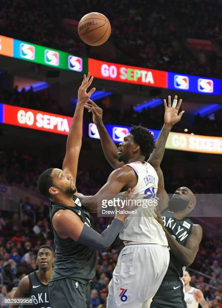 Joel Embiid of the Philadelphia 76ers gets off a shot between Jahlil Okafor and Quincy Acy of the Brooklyn Nets at the Wells Fargo Center on March 16...