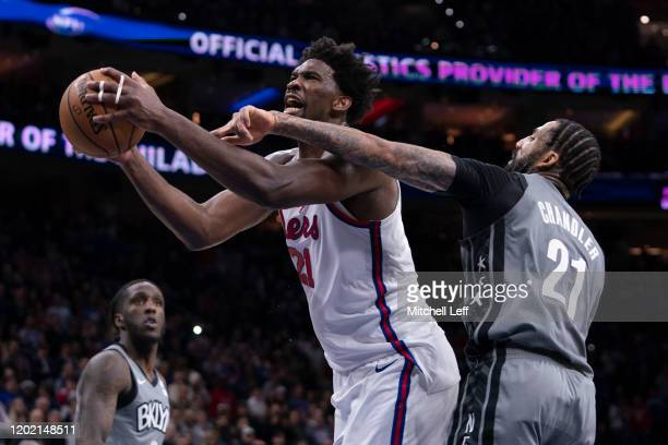 Joel Embiid of the Philadelphia 76ers goes up for a shot and is fouled by Wilson Chandler of the Brooklyn Nets in overtime at the Wells Fargo Center...