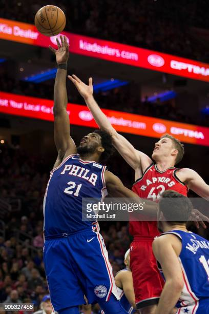 Joel Embiid of the Philadelphia 76ers grabs a rebound against Jakob Poeltl of the Toronto Raptors in the fourth quarter at the Wells Fargo Center on...