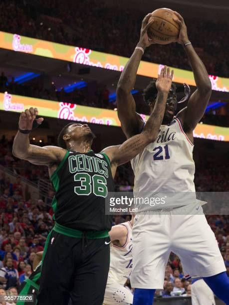 Joel Embiid of the Philadelphia 76ers grabs a rebound and has his mask broken as he fouled by Marcus Smart of the Boston Celtics in the second...