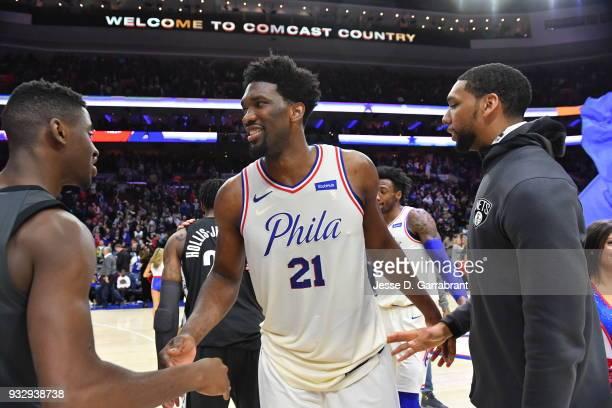 Joel Embiid of the Philadelphia 76ers greets Caris LeVert and Jahlil Okafor of the Brooklyn Nets at the Wells Fargo Center on March 16 2018 in...