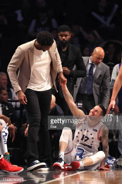 Joel Embiid of the Philadelphia 76ers helps JJ Redick to his feet in the fourth quarter against the Brooklyn Nets during game three of Round One of...