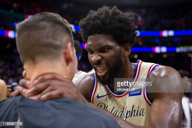 Joel Embiid of the Philadelphia 76ers jokes around with his former teammate TJ McConnell of the Indiana Pacers at the Wells Fargo Center on November...