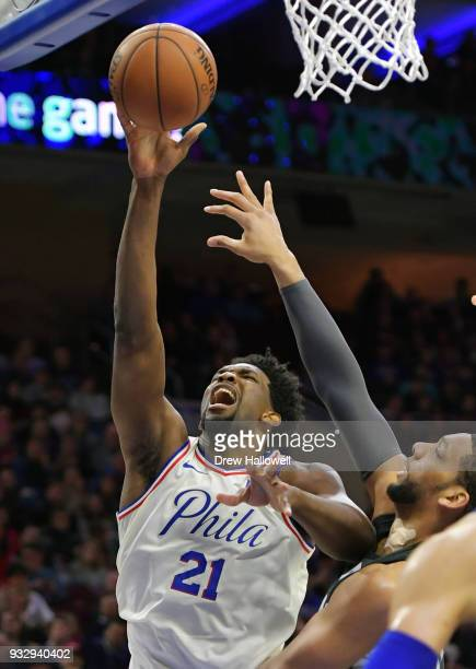 Joel Embiid of the Philadelphia 76ers lays up a shot over Jahlil Okafor of the Brooklyn Nets at the Wells Fargo Center on March 16 2018 in...