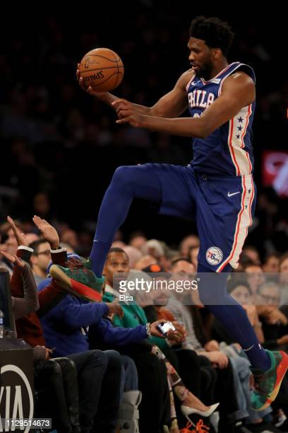 Joel Embiid of the Philadelphia 76ers leaps over the first row in attempt to keep the ball in bounds in the second half against the New York Knicks...