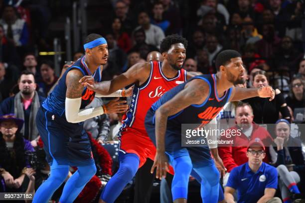 Joel Embiid of the Philadelphia 76ers looks on against Carmelo Anthony and Paul George of the Oklahoma City Thunder at Wells Fargo Center on December...
