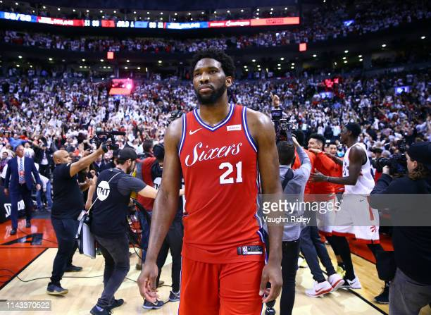Joel Embiid of the Philadelphia 76ers looks on as Kawhi Leonard of the Toronto Raptors celebrates with teammates after sinking a buzzer beater to win...