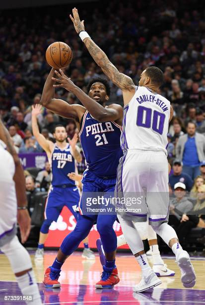 Joel Embiid of the Philadelphia 76ers looks to shoot over Willie CauleyStein of the Sacramento Kings during an NBA basketball game at Golden 1 Center...