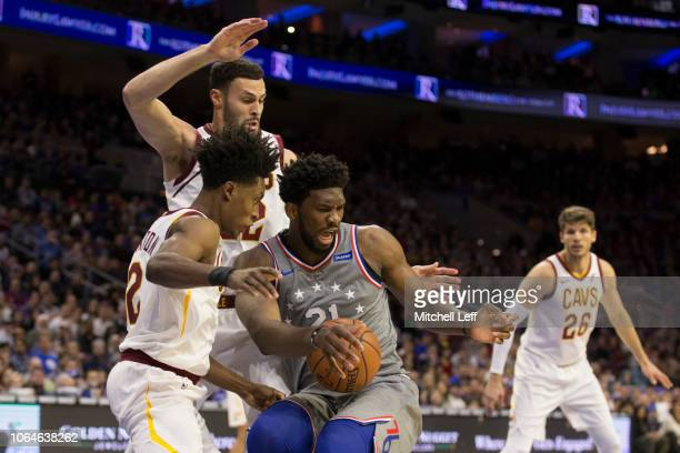 Joel Embiid of the Philadelphia 76ers loses control of the ball against Collin Sexton and Larry Nance Jr #22 of the Cleveland Cavaliers in the first...
