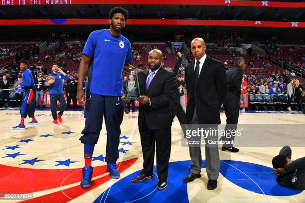 Joel Embiid of the Philadelphia 76ers presents Kevin Johnson trainer of the year award prior to the game against the Oklahoma City Thunder at Wells...