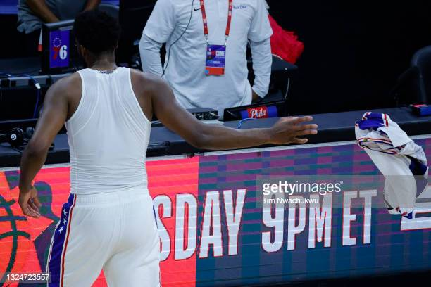 Joel Embiid of the Philadelphia 76ers takes off his jersey after losing to the Atlanta Hawks during Game Seven of the Eastern Conference Semifinals...