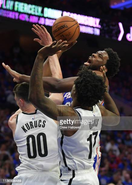 Joel Embiid of the Philadelphia 76ers tries to get a shot off over Rodions Kurucs and Ed Davis of the Brooklyn Nets in the second half during Game...