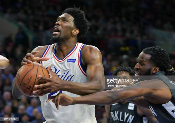 Joel Embiid of the Philadelphia 76ers tries to get off a shot while getting the ball knocked away by DeMarre Carroll of the Brooklyn Nets at the...