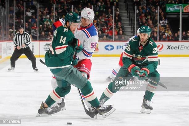Joel Eriksson Ek and Daniel Winnik of the Minnesota Wild battle for the puck with Nick Holden of the New York Rangers during the game at the Xcel...