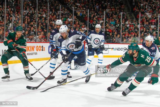 Joel Eriksson Ek and Daniel Winnik of the Minnesota Wild battle for the puck with Patrik Laine Dustin Byfuglien and Paul Stastny of the Winnipeg Jets...