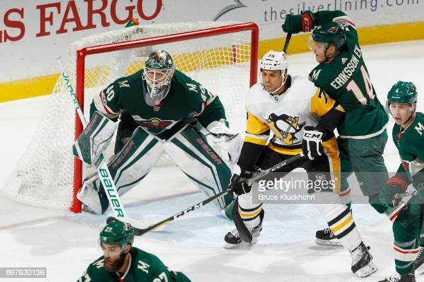 Joel Eriksson Ek and goalie Devan Dubnyk of the Minnesota Wild defend against Ryan Reaves of the Pittsburgh Penguins during the game at the Xcel...