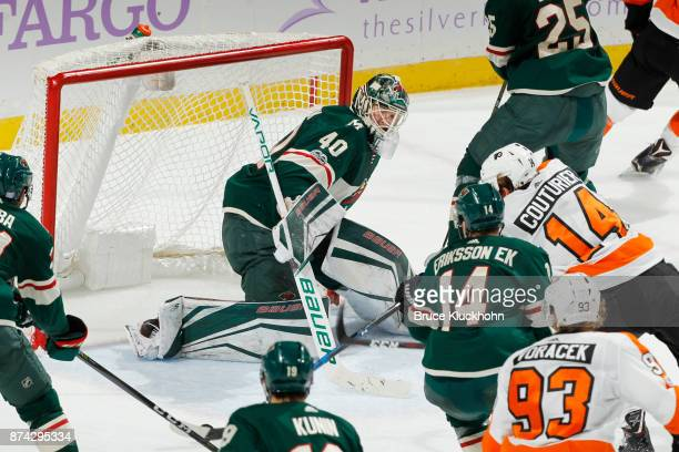 Joel Eriksson Ek and goalie Devan Dubnyk of the Minnesota Wild defend their goal against Sean Couturier of the Philadelphia Flyers during the game at...