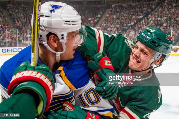 Joel Eriksson Ek of the Minnesota Wild and Brayden Schenn of the St Louis Blues battle for the puck during the game at the Xcel Energy Center on...