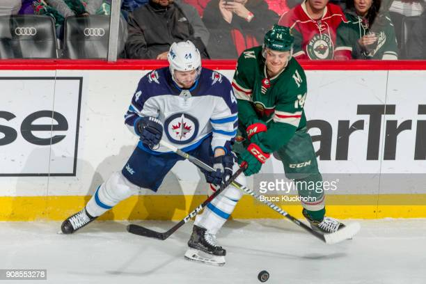 Joel Eriksson Ek of the Minnesota Wild and Josh Morrissey of the Winnipeg Jets battle for the puck during the game at the Xcel Energy Center on...