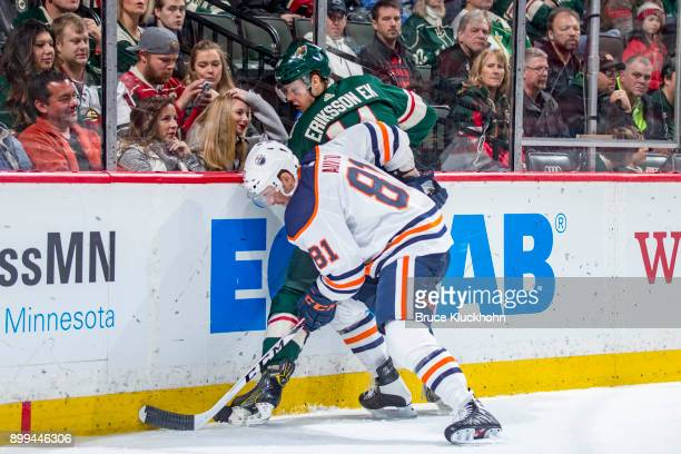 Joel Eriksson Ek of the Minnesota Wild and Yohann Auvitu of the Edmonton Oilers battle for the puck along the boards during the game at the Xcel...