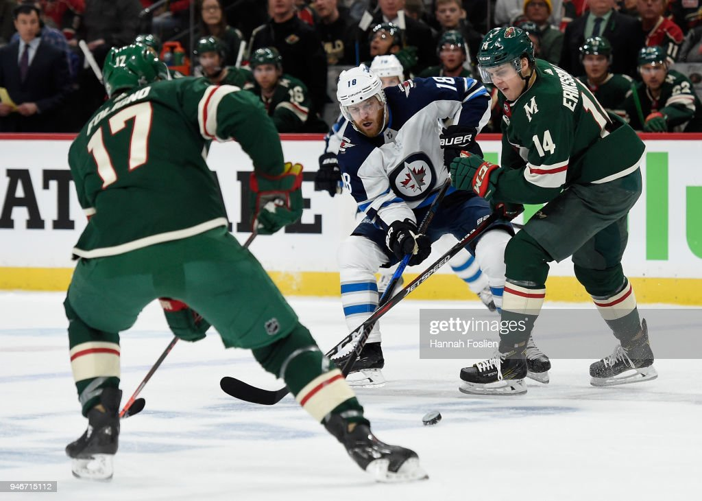 Joel Eriksson Ek #14 of the Minnesota Wild gets the puck away from Bryan Little #18 of the Winnipeg Jets as teammate Marcus Foligno #17 looks on during the first period in Game Three of the Western Conference First Round during the 2018 NHL Stanley Cup Playoffs at Xcel Energy Center on April 15, 2018 in St Paul, Minnesota. The Wild defeated the Jets 6-2.