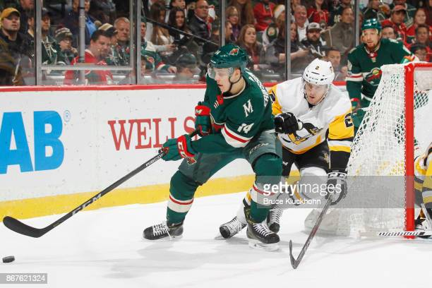 Joel Eriksson Ek of the Minnesota Wild handles the puck with Chad Ruhwedel of the Pittsburgh Penguins defending during the game at the Xcel Energy...