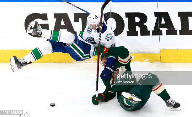 Joel Eriksson Ek of the Minnesota Wild is called for holding on this play as he takes down Loui Eriksson of the Vancouver Canucks in the third period...