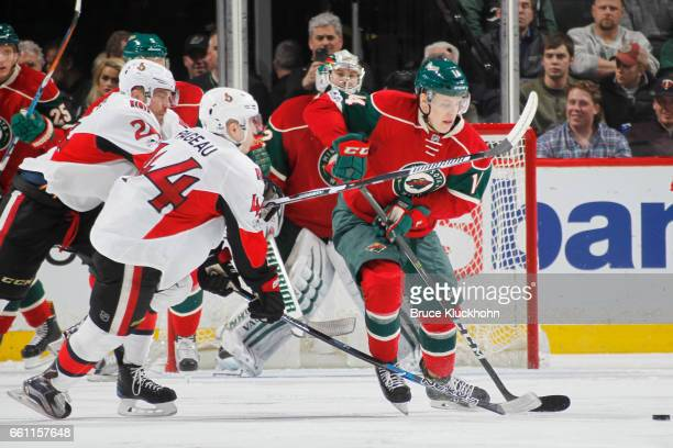 Joel Eriksson Ek of the Minnesota Wild is tripped by JeanGabriel Pageau of the Ottawa Senators during the game on March 30 2017 at the Xcel Energy...