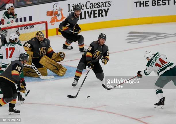 Joel Eriksson Ek of the Minnesota Wild scores an overtime goal past Alec Martinez and Marc-Andre Fleury of the Vegas Golden Knights to win Game One...