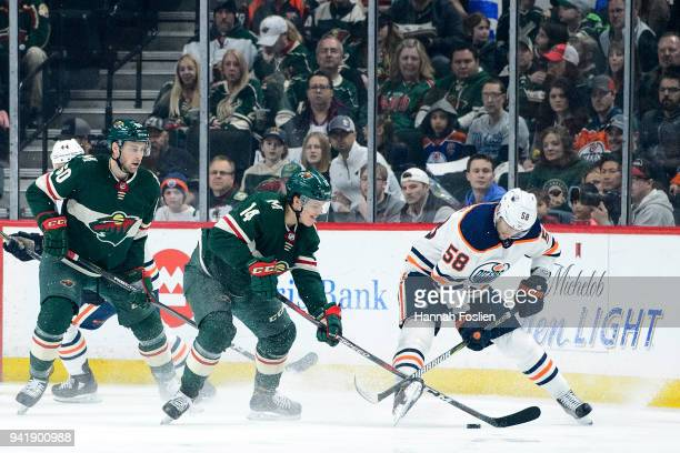 Joel Eriksson Ek of the Minnesota Wild takes the puck from Anton Slepyshev of the Edmonton Oilers as teammate Carson Soucy looks on during the game...