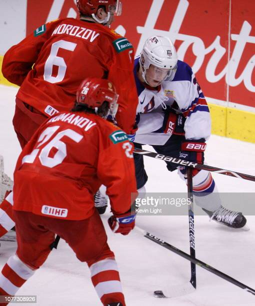 Joel Farabee of the United States skates with the puck while being chased by Ilya Morozov and Alexander Romanov of Russia during a semifinal game at...