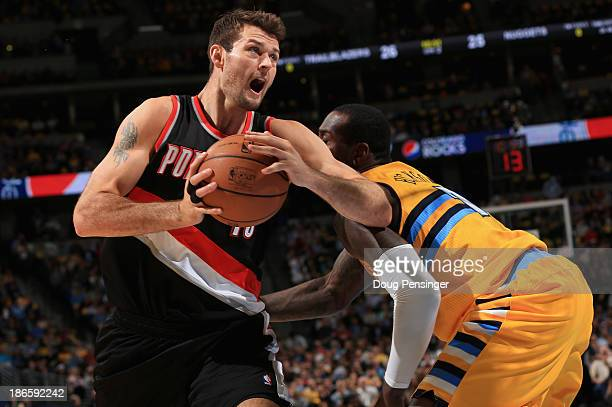Joel Freeland of the Portland Trail Blazers controls the ball against JJ Hickson of the Denver Nuggets at Pepsi Center on November 1 2013 in Denver...
