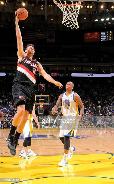 Joel Freeland of the Portland Trail Blazers dunks against the Golden State Warriors on October 24 2013 at Oracle Arena in Oakland California NOTE TO...