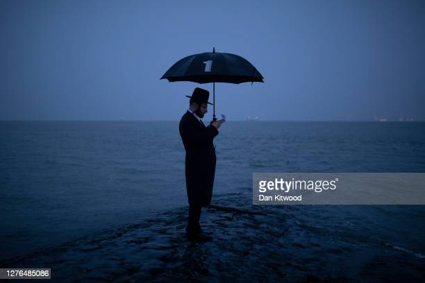 Joel Friedman and his family observe Tashlich beside the seafront at dusk on September 24 2020 in Canvey Island England The atonement ritual of...
