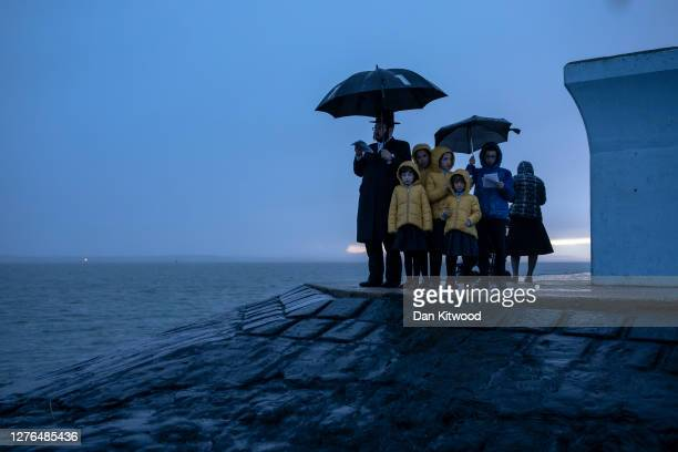 Joel Friedman and his family observe Tashlich beside the seafront at dusk on September 24, 2020 in Canvey Island, England. The atonement ritual of...