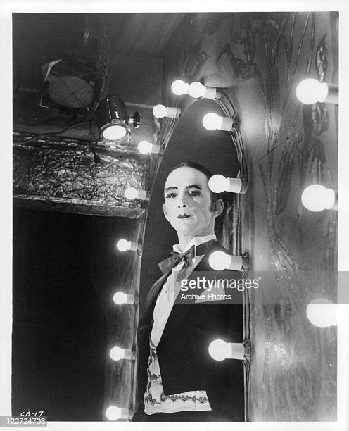 Joel Grey in full makeup looking at his reflection in a welllit mirror in a scene from the film 'Cabaret' 1972
