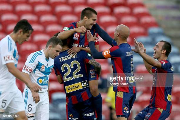 Joel Griffiths of the Jets celebrates a goal with teammates Ruben Zadkovich and Adam Taggart with Victory players Leigh Broxham and Mark Milligan...
