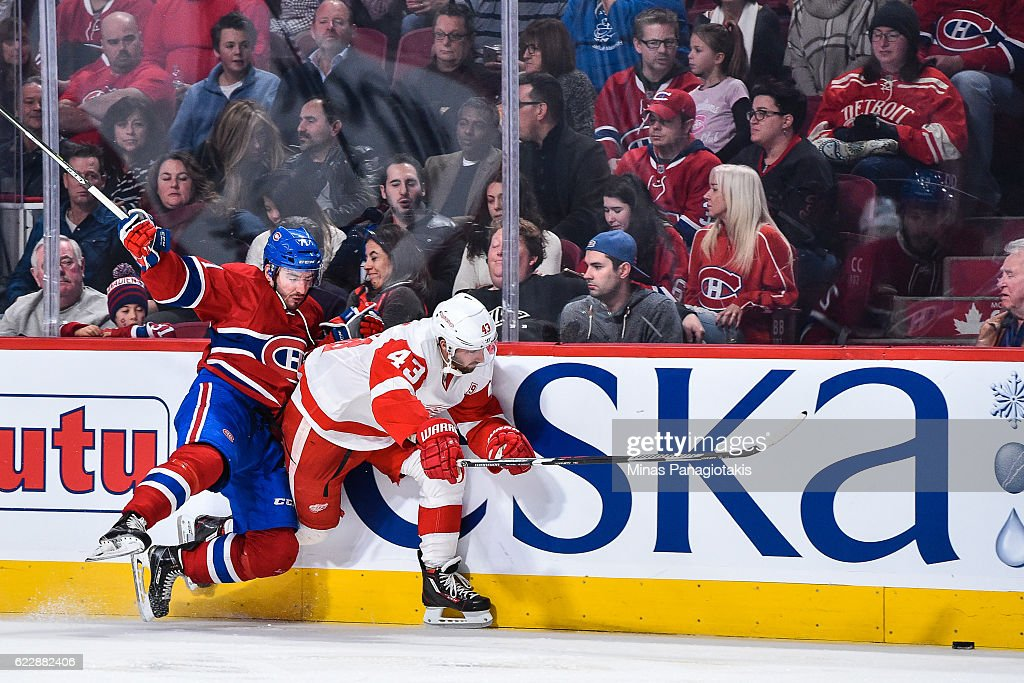 Joel Hanley #71 of the Montreal Canadiens falls behind Darren Helm #43 of the Detroit Red Wings during the NHL game at the Bell Centre on November 12, 2016 in Montreal, Quebec, Canada. The Montreal Canadiens defeated the Detroit Red Wings 5-0.