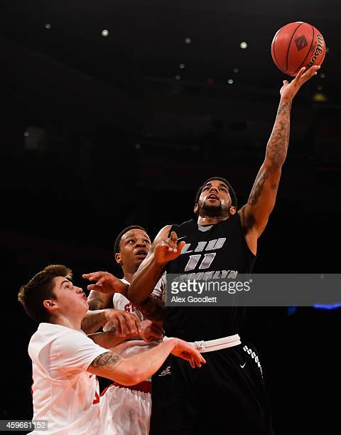 Joel Hernandez of the LIU Brooklyn Blackbirds attempts a shot over Rayshaun McGrew and Kameron Mitchell of the Stony Brook Seawolves in the second...