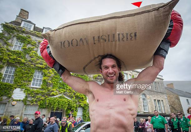 Joel Hicks carries a woolsack up the steep Gumstool Hill in the centre of Tetbury on May 25 2015 in Gloucestershire England The race between two...