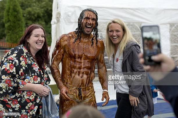 Joel Hicks poses for a photograph with supporters after winning the men's title in the 8th annual World Gravy Wrestling Championships at the Rose n...