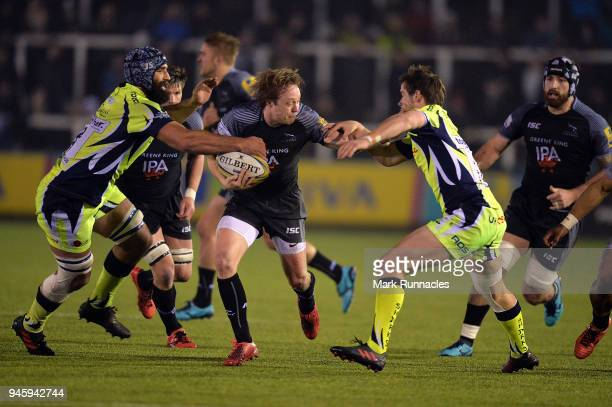 Joel Hodgson of Newcastle Falcons is tackled by AJ MacGinty and Josh Strauss of Sale Sharks during the Aviva Premiership match between Newcastle...