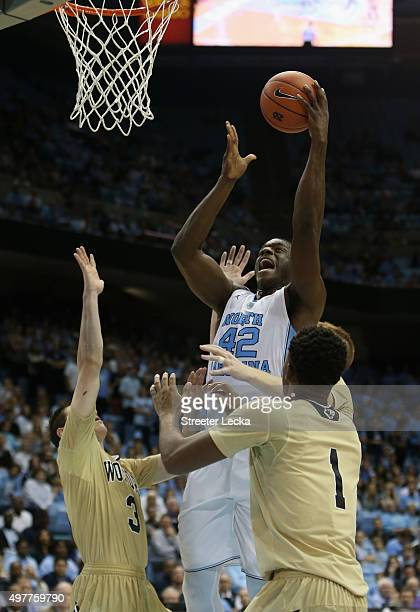 Joel James of the North Carolina Tar Heels shoots over teammates Fletcher Magee and Derrick Brooks of the Wofford Terriers during their game at Dean...