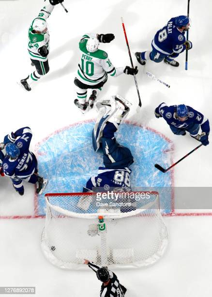 Joel Kiviranta and Corey Perry of the Dallas Stars react after goaltender Andrei Vasilevskiy of the Tampa Bay Lightning couldn't make the save on a...
