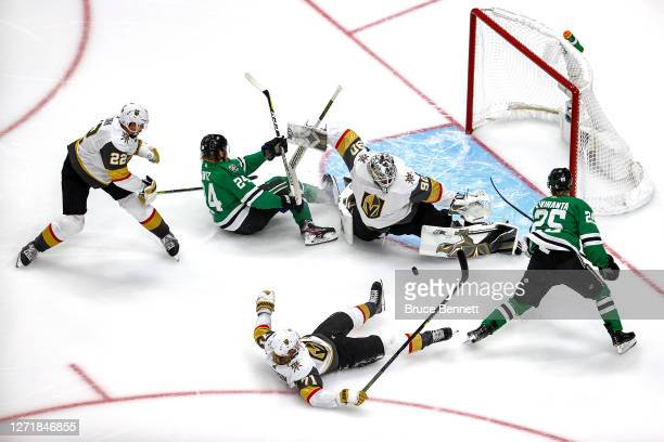 Joel Kiviranta of the Dallas Stars attempts a shot on Robin Lehner of the Vegas Golden Knights as Nick Holden checks Roope Hintz into the goal during...