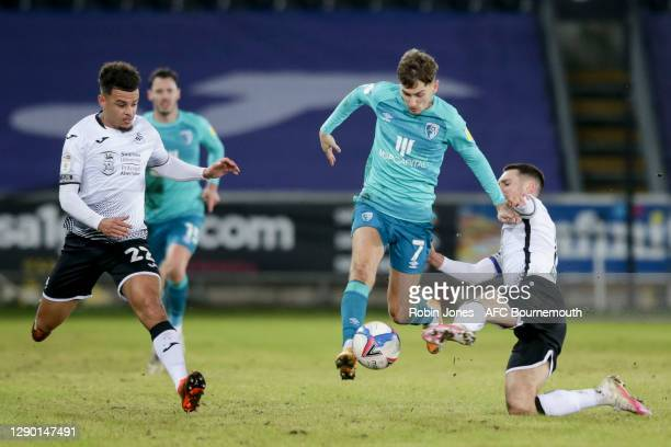 Joel Latibeaudiere and Matt Grimes of Swansea City combine to stop David Brooks of Bournemouth during the Sky Bet Championship match between Swansea...