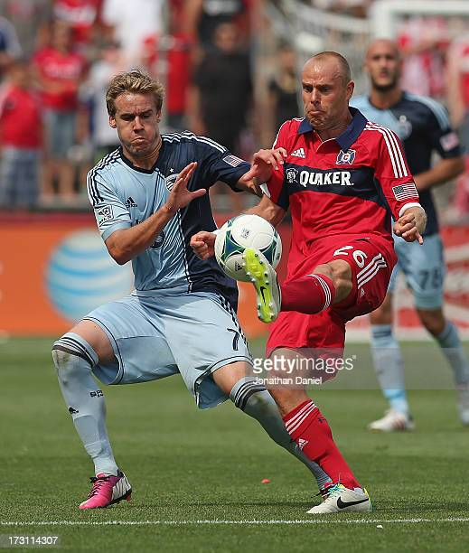 Joel Lindpere of the Chicago Fire kicks the ball away from Chance Myers of Sporting Kansas City during an MLS match at Toyota Park on July 7 2013 in...